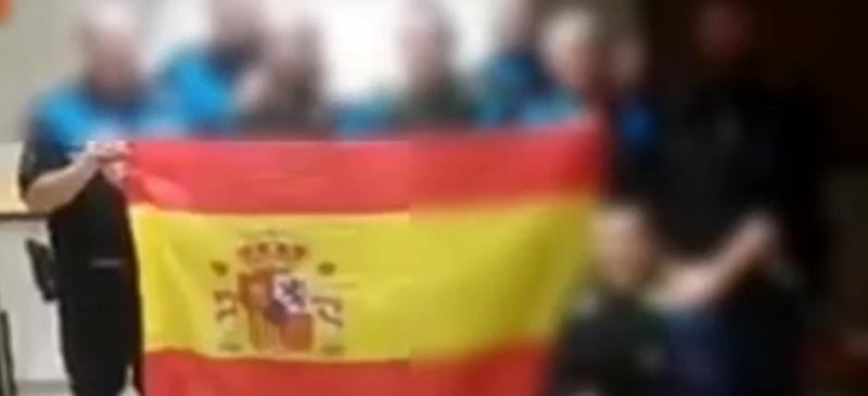 Foto portada: el grup de policies, amb la bandera espanyola, durant el servei.