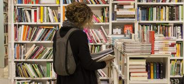 Noia fullejant un llibre a la Llar del Llibre. Autor: M. Tornel.