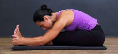 Foto portada: una dona practicant ioga, a casa seva.