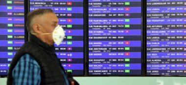 Imatge d'un viatger amb mascareta passant per davant d'una de les pantalles d'informació del Prat el 13 de març de 2020. (Horitzontal)