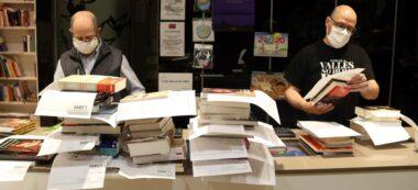 Imatge de dos empleats de La Llar del Llibre de Sabadell preparant comandes per entregar a les llars. Imatge del 21 d'abril de 2020. (Horitzontal)