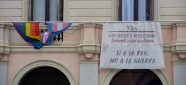 Foto portada: la bandera irisada i una a favor dels refugiants, a la plaça del doctor Robert. Autor: David B.